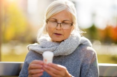 Senior woman checking label on blood pressure pills blood pressure drugs