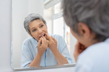 Senior woman cleaning teeth with dental floss