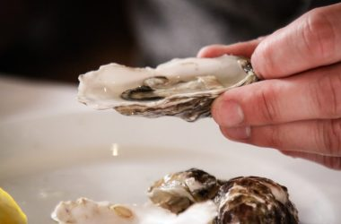 Hand holding zinc rich oyster which could combat high blood pressure