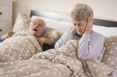 Senior man with sleep apnea snores as wife covers ears