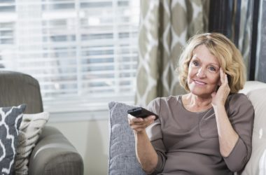 Senior woman sitting watching TV in living room social distancing