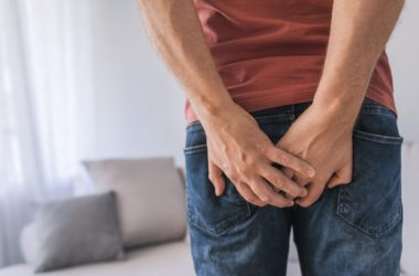 Man with painful hemorrhoids has his hands on his backside