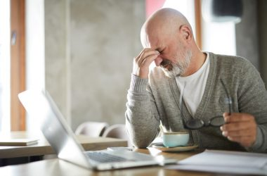 Senior man experiencing eye strain from staring at computer