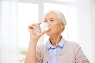 Senior woman drinks water to prevent dehydration linked falls