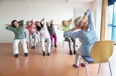 Seniors doing chair yoga to reduce hypertension-min