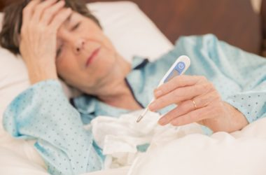 Woman sick with flu lies in bed with tissue and thermometer
