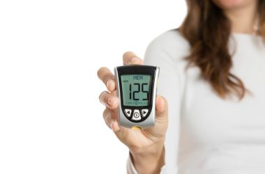 Woman with good blood sugar control from L. casei probiotic holds glucometer