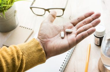 Man holding two acetaminophen painkillers in his hand