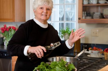 Mature woman sautes vegetables in olive oil reducing risk of heart attacks