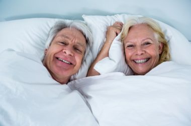 Senior couple smiling in bed after using maca to boost libido