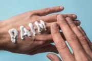 The word pain written in pain cream on a hand