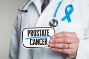 Doctor in lab coat holding sign reading prostate cancer
