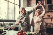 Senior couple dancing in kitchen with glasses of alcohol on table