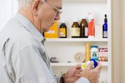 Senior man reading label on aspirin bottle