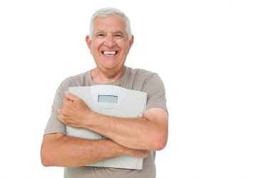 Smiling senior man holding scale happy about his weight loss