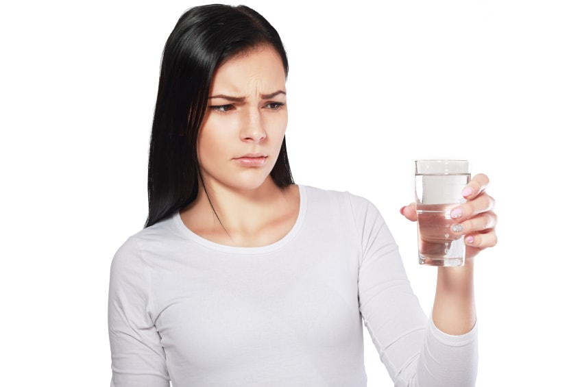 Woman staring suspiciously at a glass of arsenic laced tap water