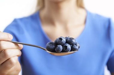 Close up of woman holding a spoon of blueberries which support arteries