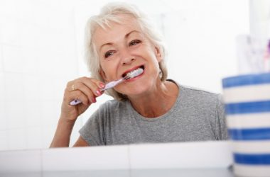 Senior woman brushing teeth to lower Alzheimer's disease risk