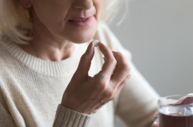 Senior woman taking metformin pill with glass of water