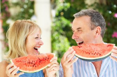 Smiling senior couple eating potassium rich watermelon for weight loss