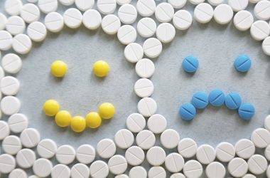 Pills forming a smiling and frowning face to illustrate antidepressants