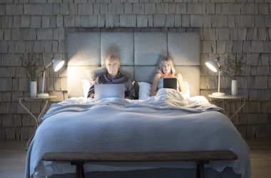 Senior couple reading digital devices in bed interfering with weight loss
