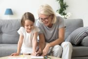 Smiling grandchild and grandmother draw to enhance memory