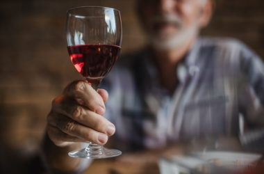Senior man holding glass of red wine with depression fighting resveratrol
