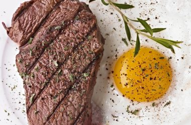 Steak and eggs sunny side up with seasoning