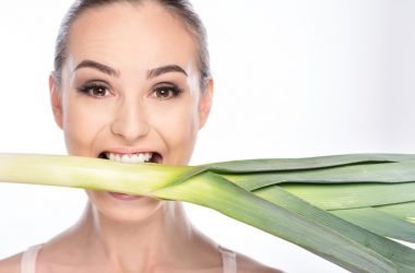 A woman biting a leek to illustrate a vegetarian diet