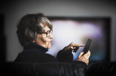 Anxious senior woman turning off TV to cure sleep problems