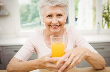 Happy senior woman having a glass of diabetes linked juice