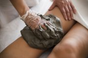 Mud being applied to knee to relieve arthritis pain