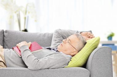 Senior man taking a nap on the sofa cutting heart risks