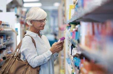 Senior woman reading label on a heartburn drug package in store