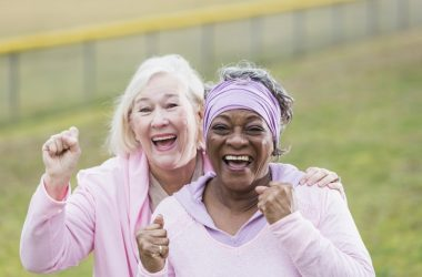 Senior breast cancer survivors smiling and cheering