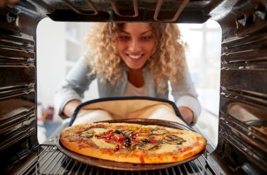 View from inside oven as woman cooks frozen pizza with trans fats