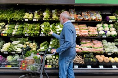 Senior man shops for leafy greens in a grocery store