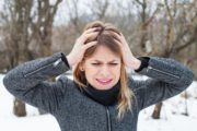 woman stands in snow holding her head because of a winter headache