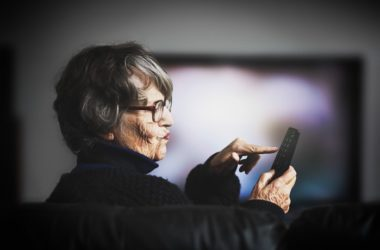 Senior woman watching TV news suffers from anxiety