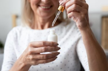 Mature woman about to use dropper of essential oil on wounds