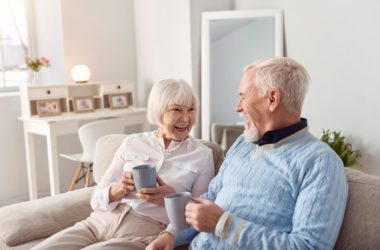 Smiling senior couple drinks coffee with caffeine to protect against an unhealthy diet