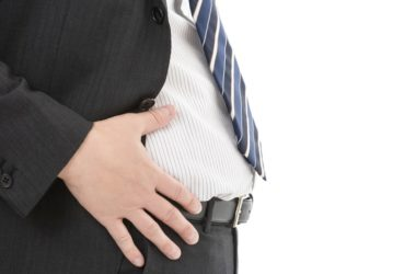 Man in suit has hand on belly fat linked to cognitive decline