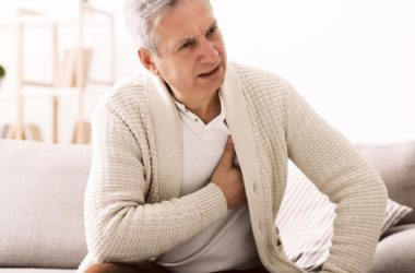 Mature man with irregular heartbeat or atrial fibrillation holds heart