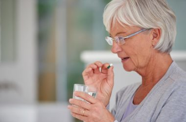 Senior woman taking a diuretic pill with a glass of water
