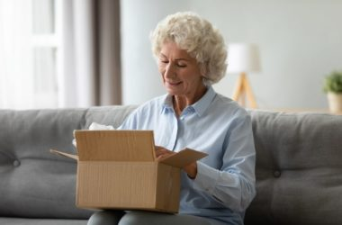Smiling senior woman opening mail package safe from coronavirus
