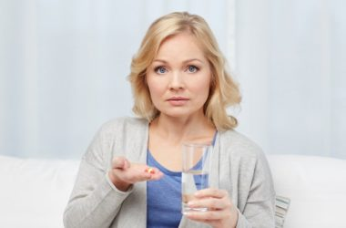 Woman about to take antibiotics with a glass of water
