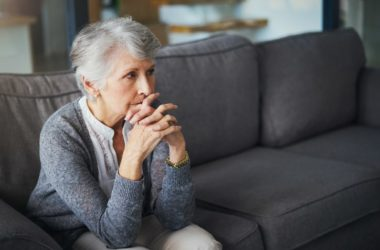 Senior woman sitting on gray sofa feeling stress and anxiety