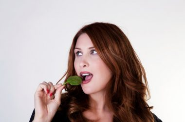 Woman about to bite into a spinach leaf to boost memory and brain power