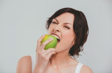 Woman biting into a fiber rich green apple which could help reduce breast cancer risk